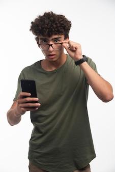 Giovane ragazzo con i capelli ricci che controlla i messaggi e viene sorpreso.