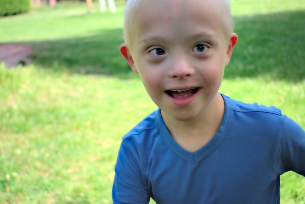 Young boy with a down syndrome who is playing in a park