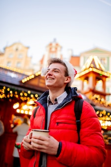 Young boy with drink on christmas market in wroclaw, poland
