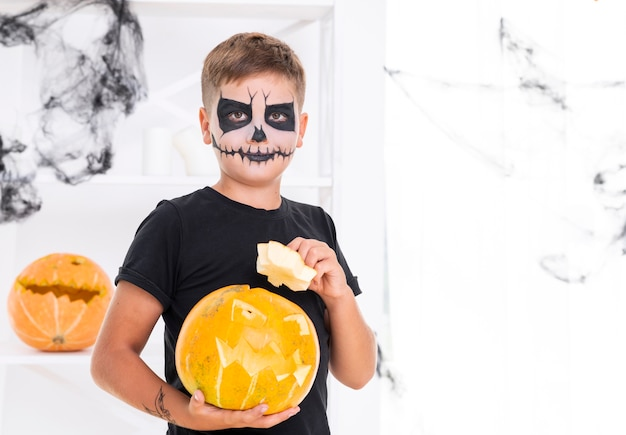 Young boy with face painted holding a pumpkin