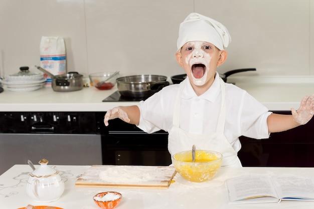 顔全体に小麦粉を持ち、口を大きく開けてキッチンで楽しんでいる少年