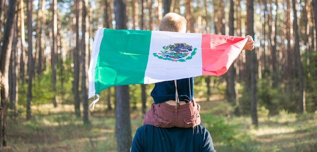 Young boy with his father holding the mexican flag