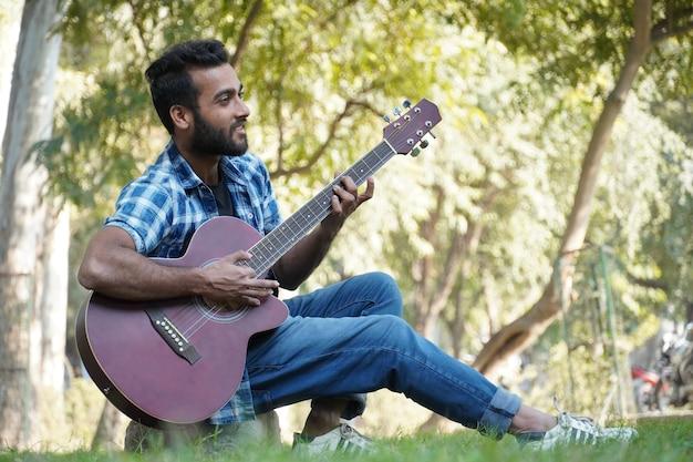 彼のギターとギターを弾く少年