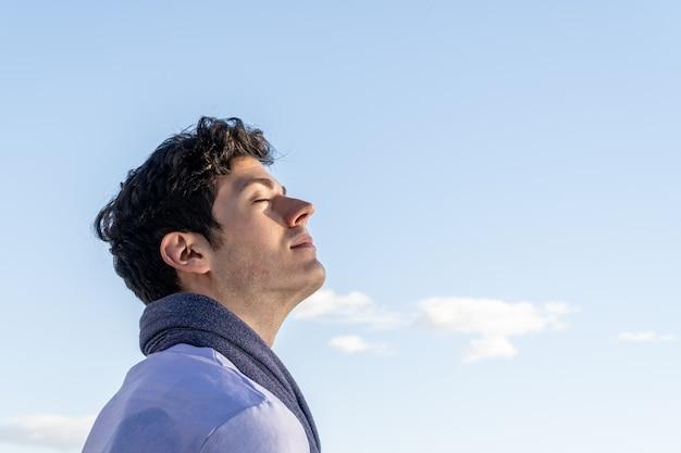 맑은 날에 머리를 하늘로 향하고 눈을 감고 있는 어린 소년