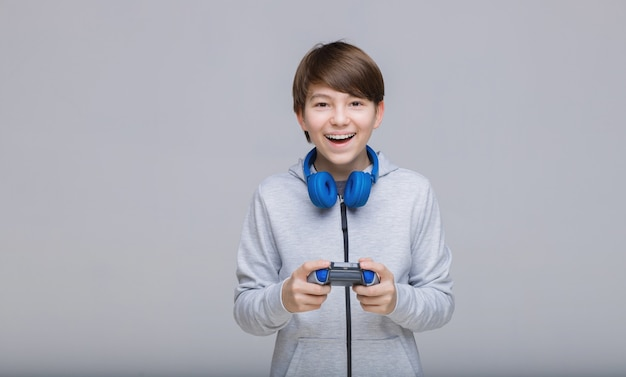 Young boy with joystick in hands playing in video game