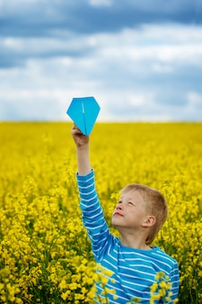 Young boy with paper airplane against blue sky