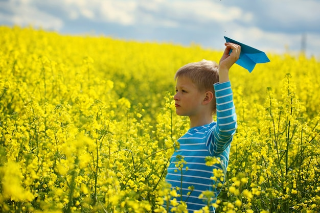 Young boy with paper plane against blue sky and yellow field flo