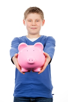 Young boy with pink piggybank on white space