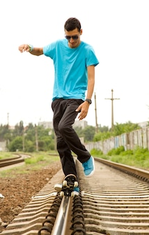Young boy with skateboard at railway.