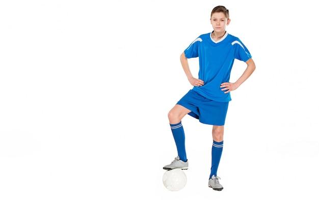 フライングキックを行うサッカーボールの少年