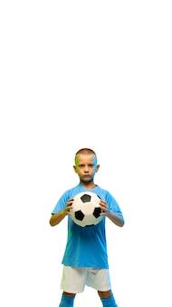 白いスタジオの背景に分離されたサッカーボール、コピースペースと垂直チラシを持つ少年
