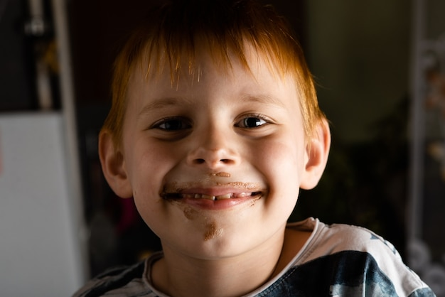A young boy with a soiled ice cream face.