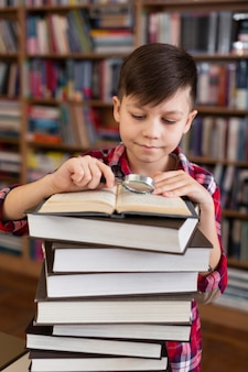 Young boy with stack of books reading