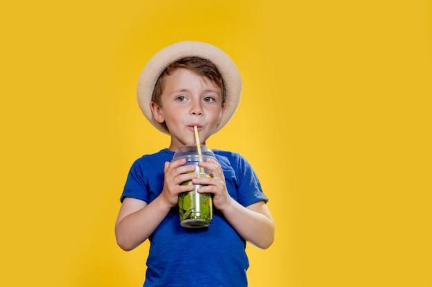Молодой мальчик в соломенной шляпе и синей футболке пьет мохито в пластиковом стаканчике на желтом фоне
