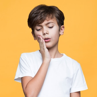 Young boy with tooth pain on yellow background