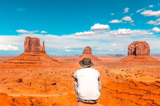 A young boy with white t-shirt sitting in the center of the photo on a stone in the monument valley national park