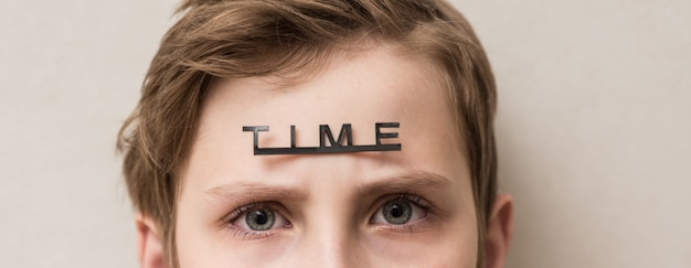 Young boy with the word time on his forehead