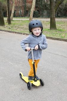 公園で黄色のスクーターを持つ少年