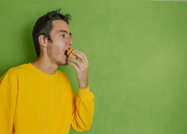 Молодой мальчик в желтой толстовке, кусающий кекс, который он держит в руке, зеленый фон