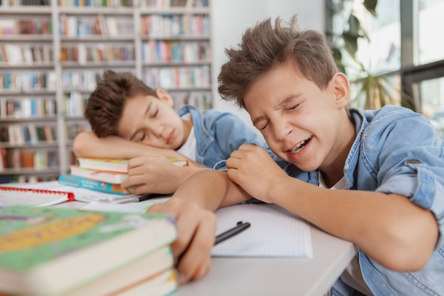 Young boy yawning, falling asleem at the library after studying with his twin brother