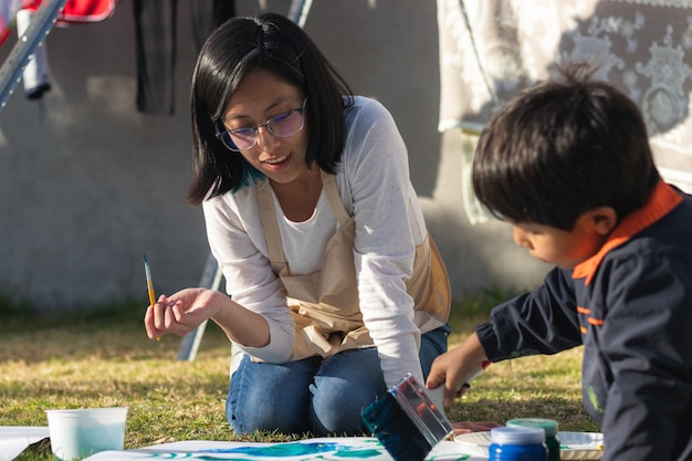 Young boy and young woman painting with a brush and brushes on a white surface, wearing smocks, in the courtyard on a sunny day with clothes lying in the background