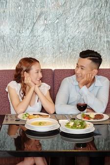 레스토랑에서 저녁을 먹을 때 서로를 바라보며 사랑에 빠진 젊은 남자친구와 여자친구