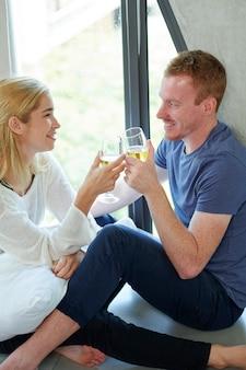 젊은 남자 친구와 여자 친구는 샴페인 잔을 손에 들고 창틀에 앉아 술을 즐기고 있습니다.