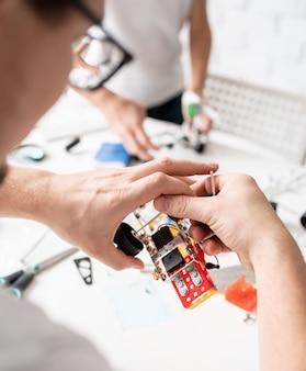 Молодые парни и веселятся, собирая машины-роботы вместе в мастерской