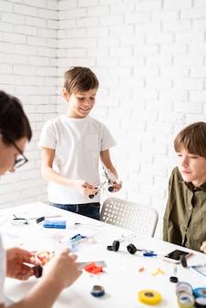 어린 소년과 워크숍에서 함께 로봇 자동차를 만드는 재미