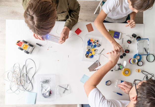 Молодые мальчики и учитель весело конструируют автомобили-роботы в мастерской, вид сверху