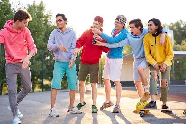若い男の子はスポーツ遊び場で屋外で楽しんでいます