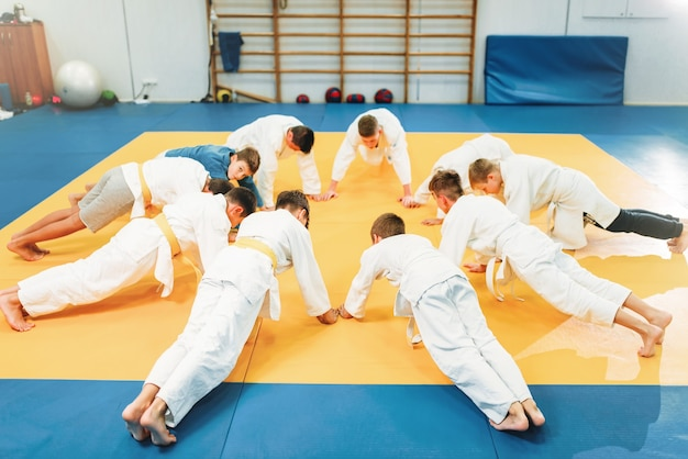 Young boys in kimono makes push up exercise, kid judo. young fighters in gym, martial art