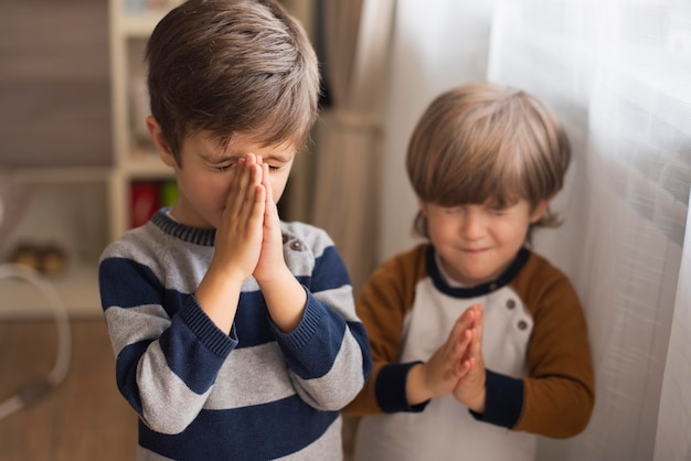 自宅で一緒に祈る少年