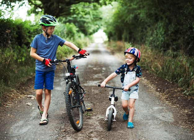Young boys pushing their bikes