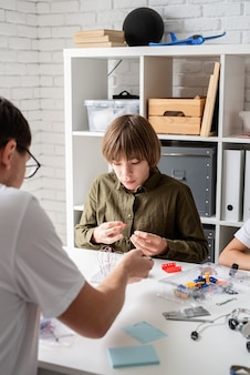 Young boys and teacher having fun constructing robot cars together at the workshop