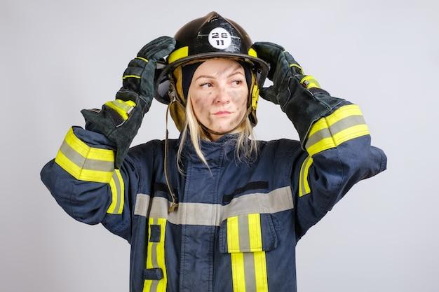 消防士の制服を着た若い勇敢な女性は彼女の頭にヘルメットをかぶる