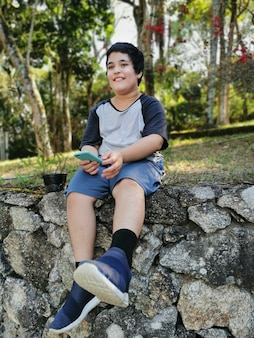 Young brazilian boy smile holding his mobile.