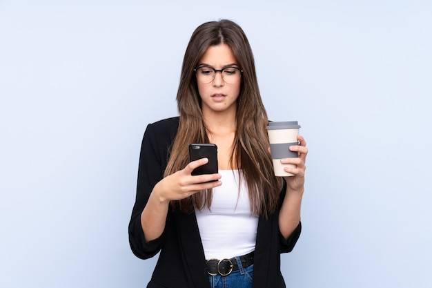 Young brazilian business woman holding coffee to take away over isolated blue background