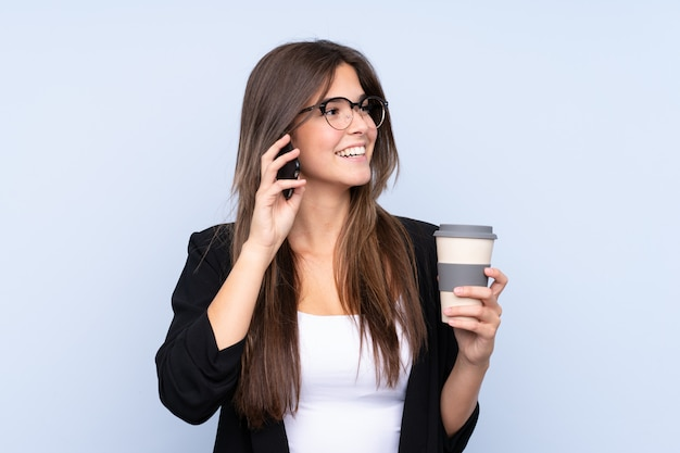 Young brazilian business woman holding coffee to take away and talking to mobile