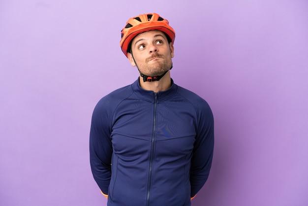 紫色の背景に分離され、見上げるブラジルの若いサイクリストの男