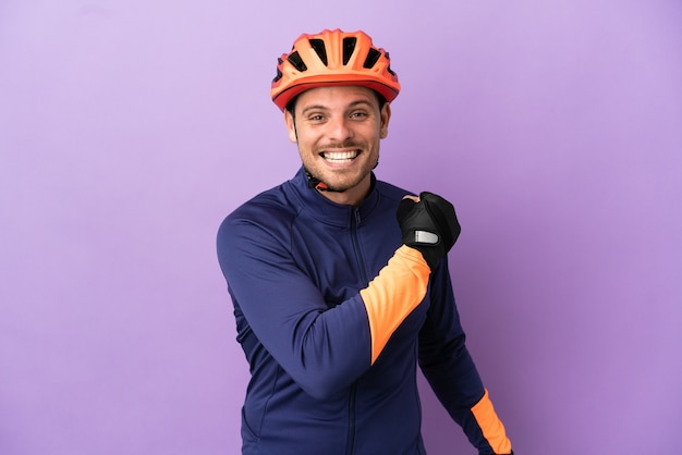 Молодой бразильский велосипедист, изолированные на фиолетовом фоне, празднует победу