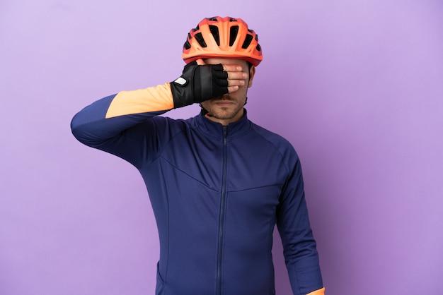 Молодой бразильский велосипедист человек изолирован на фиолетовом фоне, закрывая глаза руками. не хочу что-то видеть