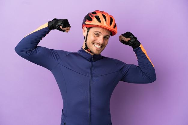 Молодой бразильский велосипедист, изолированные на фиолетовом фоне, делает сильный жест
