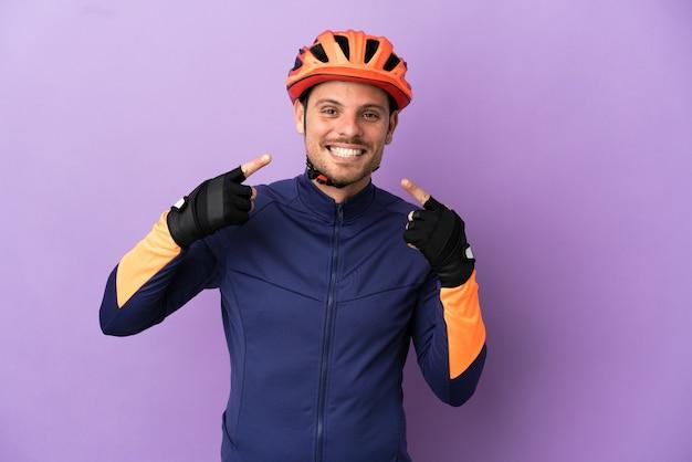 Молодой бразильский велосипедист изолирован на фиолетовом фоне, показывая жест рукой вверх