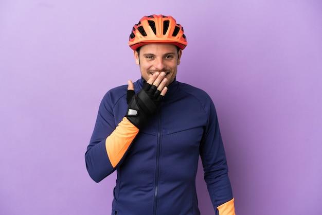 Молодой бразильский велосипедист мужчина изолирован на фиолетовом фоне, счастливый и улыбающийся, прикрывая рот рукой