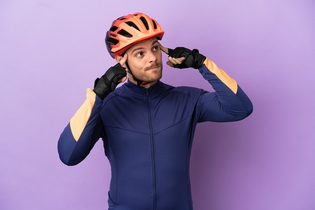Молодой бразильский велосипедист человек изолирован на фиолетовом фоне с сомнениями и мышлением