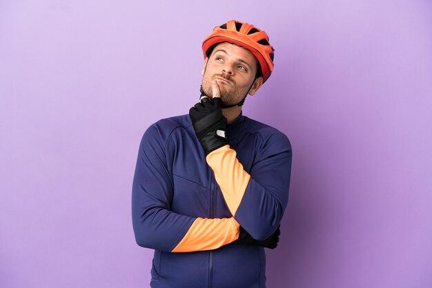 Молодой бразильский велосипедист человек изолирован на фиолетовом фоне, сомневаясь, глядя вверх