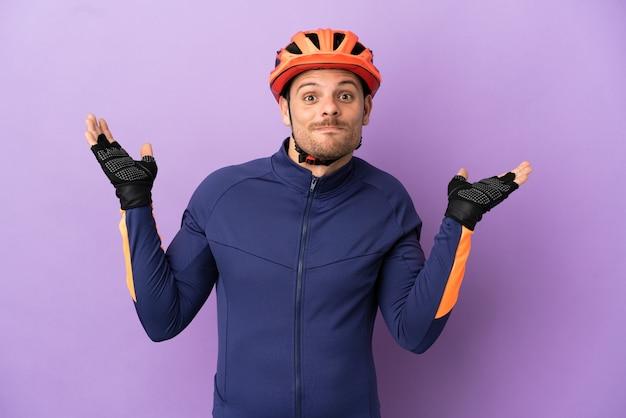 Молодой бразильский велосипедист мужчина изолирован на фиолетовом фоне, сомневаясь, поднимая руки