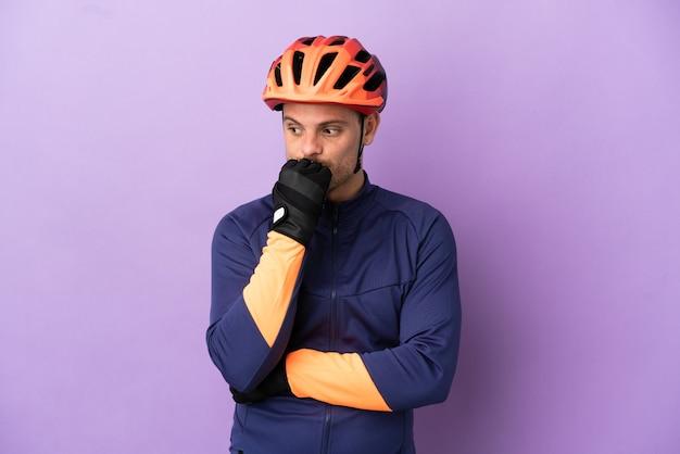 Молодой бразильский велосипедист человек изолирован на фиолетовом фоне с сомнениями