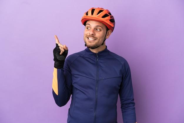 Молодой бразильский велосипедист изолирован на фиолетовом фоне, намереваясь реализовать решение, подняв палец вверх